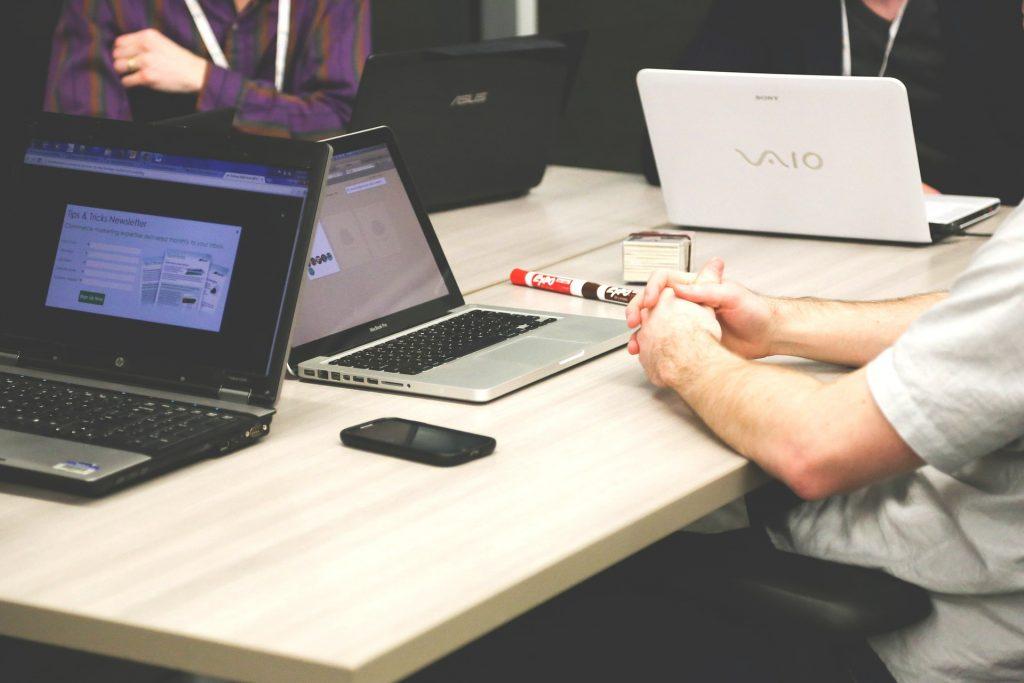 homme assis en face de trois ordinateurs autour d'une table en bois